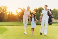 A woman in a bright outfit, a girl in a light dress and a man in a white suit with a bag for golf clubs walking along the golf course. A woman shows her hand to the side