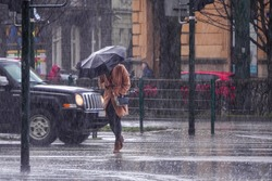 A woman in a brown coat under an umbrella crosses a busy street in heavy rain. Heavy precipitation in the city. Flooding of city streets.