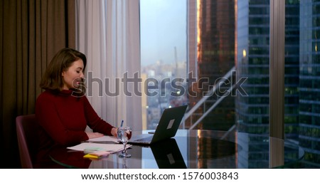 a woman in a Burgundy dress sits at a round table near a large window. she communicates through a video link on a laptop and makes recordings. behind the window you can see high-rise city buildings #1576003843