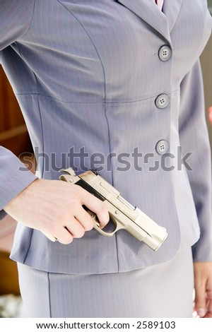 A woman in a business suit holds a gun by her side