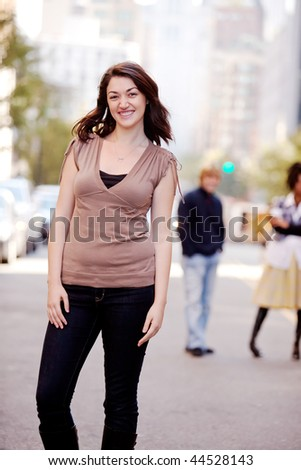 A woman in a city setting with friends in the background