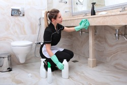 A woman in a cleaning lady's uniform can have a marble countertop in the bathroom. Plastic bottles of detergent on the floor. The concept of the hotel business.