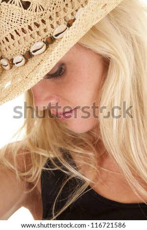 A woman in a cowgirl hat is looking down.  A close up of her face.