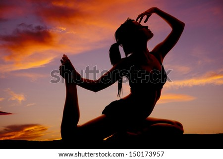 A woman in a dance or yoga pose in the sunset