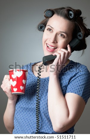 A woman in a domestic role happily talking on the phone at home.