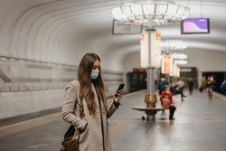 A woman in a face mask to avoid the spread of coronavirus is holding a smartphone at a subway station. A girl in a surgical mask on the face against COVID-19 is waiting for a train on a metro platform