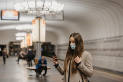A woman in a face mask to avoid the spread of coronavirus is reading news on a phone at a subway station. A girl in a surgical face mask against COVID-19 is waiting for a train on a metro platform.