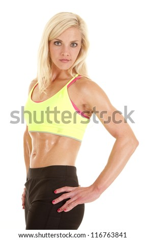 A woman in a green sports bra is standing sideways with a serious expression on her face.
