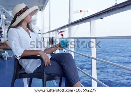 a woman in a hat and a cocktail in the summer on the liner