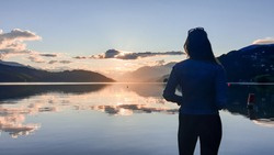 A woman in a jeans jacket standing at the shore of Millstaettersee and enjoying the sunset. The sun sets behind high Alps. Calm surface of the lake reflects the orange sky and the mountains. Meditate