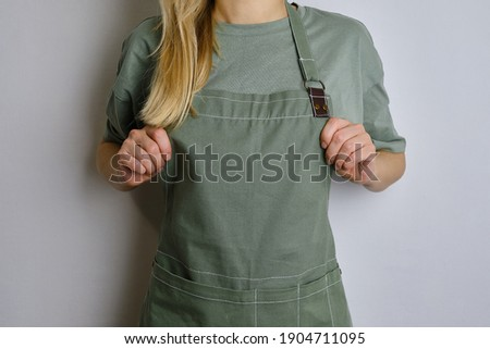 A woman in a kitchen apron. Chef work in the cuisine. Cook in uniform, protection apparel. Job in food service. Professional culinary. Green fabric apron, casual clothing. Handsome baker posing Stockfoto ©