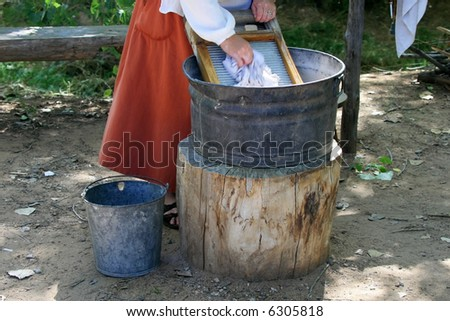 A woman in a long red skirt is washing clothes on a washboard and bucket set up by a stream.  Motion blur on hand scrubbing cloth on the board.
