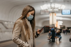 A woman in a medical face mask to avoid the spread of coronavirus is using a smartphone at the subway station. A girl in a surgical mask on the face against COVID-19 is scrolling news on her cellphone