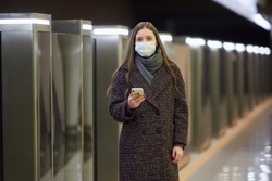 A woman in a medical face mask to avoid the spread of coronavirus is waiting for a train and holding a cellphone at the subway station. A girl in a surgical mask is keeping social distance in metro.