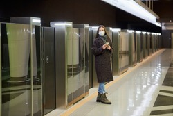A woman in a medical face mask to avoid the spread of coronavirus is waiting for a train and holding a smartphone at the subway station. A girl in a surgical mask is keeping social distance in metro.