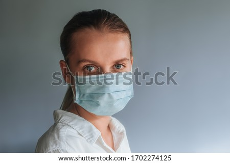 A woman in a medical mask on a light gray background