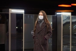 A woman in a medical mask to avoid the spread of coronavirus is standing near the departing train on the subway platform. A girl in a surgical mask is keeping social distance on a metro station.