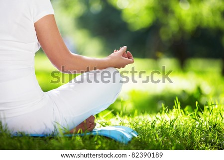 A woman in a park in the lotus position in close-up