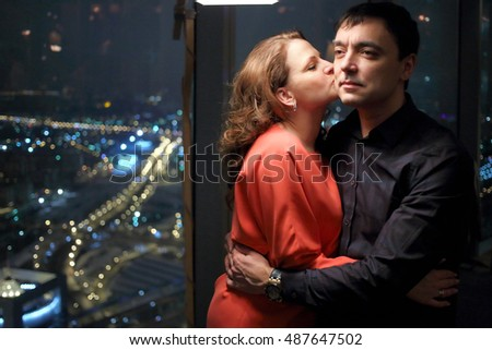 Stock Photo A woman in a red dress is kissing a man standing near a big window with a view of the city in a restaurant in the evening