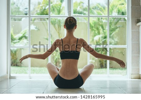 A woman in a short T-shirt and shorts sits in front of the window indoors and meditates                           #1428165995