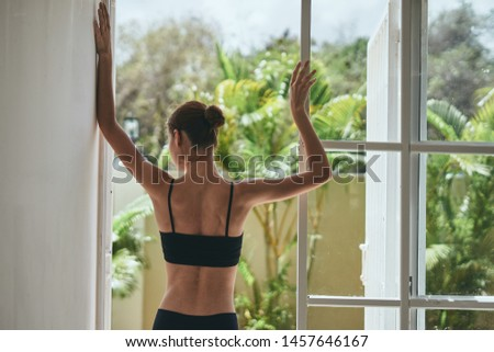 A woman in a short vest and shorts does yoga in front of a window with a room                     #1457646167