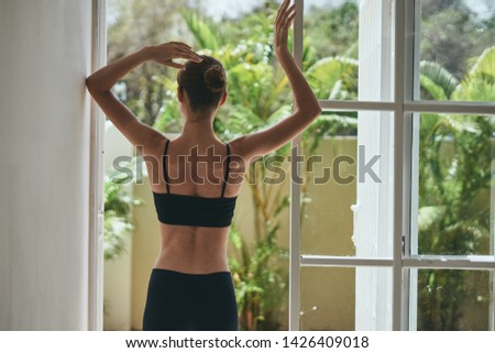 A woman in a short vest and shorts in a room near the window                  #1426409018