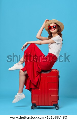 A woman in a skirt sits on a red suitcase for a vacation travel vacation
