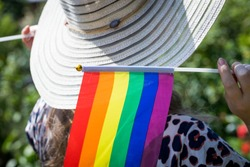 A woman in a stylish summer hat with a flag supporting the LGBT movement on her shoulder