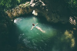 A woman in a swimsuit swims in a mountain river, The girl goes into cold water, Picturesque place of Turkey.