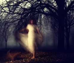 a woman in a very foggy forest