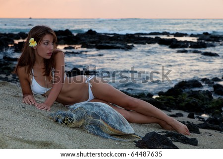 A woman in a  white bikini poses on the beach next to a resting sea turtle