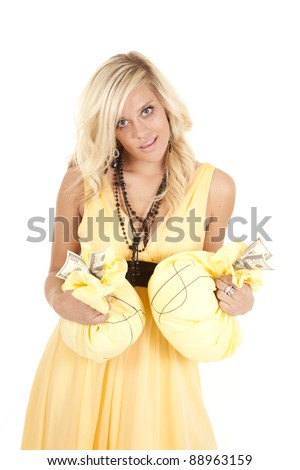 a woman in a yellow dress holding money bags with a small smile on her lips