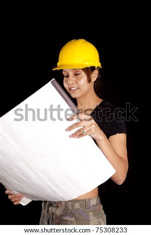 A woman in a yellow hard had is looking at some plans.