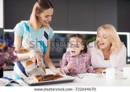 A woman in an apron is cutting a pie that she just took out of the oven. Her mother and daughter sit side by side and look at the pie