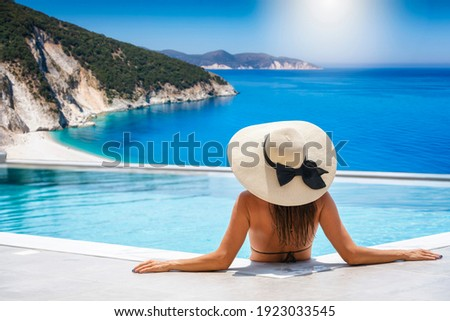 A woman in bikini and with hat sits in the swimming pool and enjoys the view to the turquoise sea of Kefalonia island, Ionian Sea, Greece, during summer holiday time