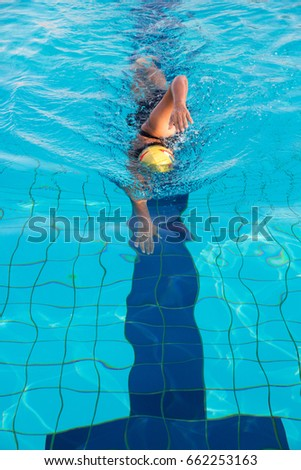 A woman in black swim suits and yellow cap is swimming in freestyle stroke (front crawl) in a swimming pool with clear and blue water.