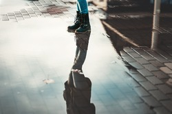A woman in boots stands near the puddles. Reflections of the sky in puddles. Lower angle. The concept of psychology and loneliness.
