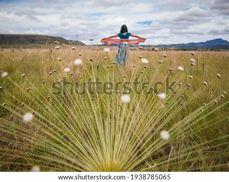 A woman in casual clothes dancing outdoors among several cerrado flowers Foto stock ©