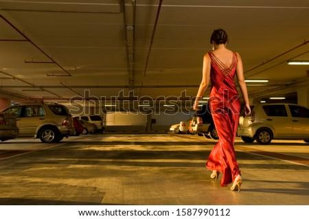 A woman in evening dress walking in a car park