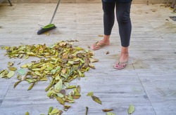 A woman in flipflops sweeping fallen leaves on tiled outdoor floor