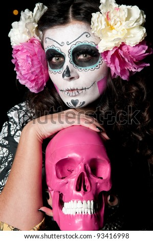 A woman in Halloween costume and skull makeup holding flowers