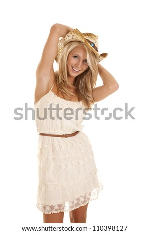 A woman in her beautiful lace dress with a smile on her face holding on to her hat.