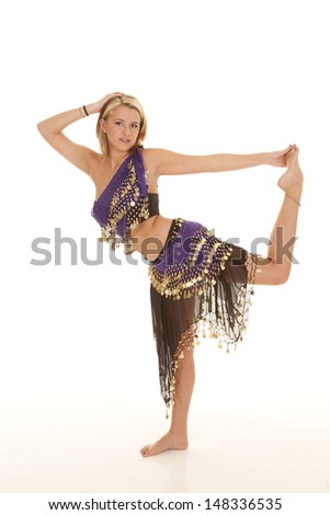 A woman in her belly dancing clothes holding on to her foot, with a small smile on her face.
