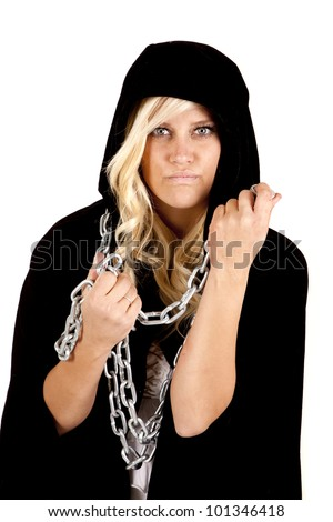 A woman in her black cape holding on to her chain with a mean expression on her face. - stock photo