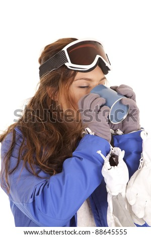 a woman in her ski clothes and goggles holding a mug of hot chocolate  enjoying every sip.