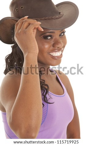 a woman in her workout top with a smile on her face holding on to the brim of her hat