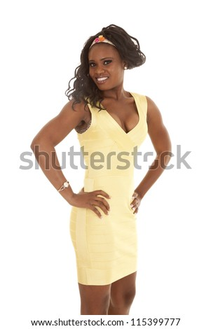 a woman in her yellow dress standing with her hands on her hips with a smile on her lips.
