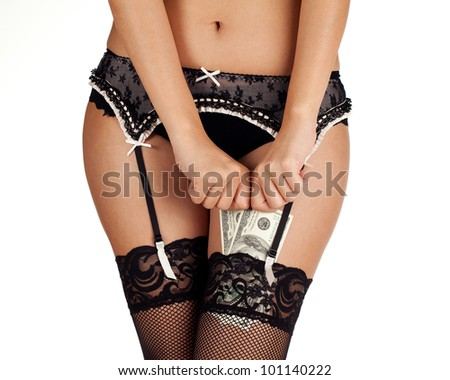 A woman in lace stockings and underwear putting money in her stockings. - stock photo