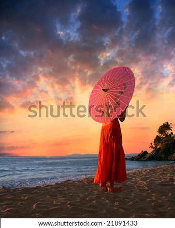 A woman in orange skirt walking on a beach - stock photo