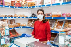A woman in rubber gloves and a medical mask stands at the workplace. In the background-shelves and shop Windows. The concept of coronovirus, quarantine and the crisis in business